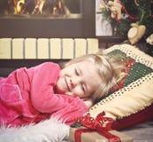 Pequeña muchacha linda que duerme debajo del árbol de navidad para S que espera Fotografía de archivo