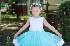Pequeña muchacha linda que lleva un vestido blanco y azul que presenta sobre el fondo de la naturaleza, niño con una guirnalda de Fotografía de archivo libre de regalías
