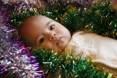 Pequeña muchacha linda que miente en cama con una Navidad Foto de archivo