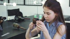 Pequeña muchacha linda que parece triste examinando su pelo dañado con los extremos partidos metrajes