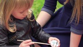Pequeña muchacha linda que pinta el huevo de Pascua cerca de padres en el parque lentamente almacen de video