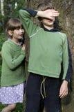 Pequeña muchacha linda que se coloca en el árbol. Fotografía de archivo libre de regalías