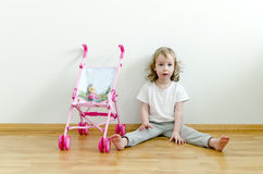 Pequeña muchacha linda que se sienta en el suelo Imagen de archivo