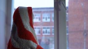 Pequeña muchacha linda que se sienta en el travesaño de la ventana, mirando hacia fuera en un paisaje urbano nevoso almacen de metraje de vídeo