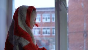 Pequeña muchacha linda que se sienta en el travesaño de la ventana, mirando hacia fuera en un paisaje urbano nevoso almacen de video