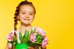 Pequeña muchacha linda que sostiene el cubo con los tulipanes rosados Imagenes de archivo