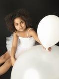 Pequeña muchacha linda que sostiene un globo Imagenes de archivo