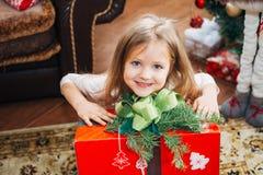 Pequeña muchacha linda que sostiene un regalo de la Navidad imagenes de archivo
