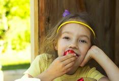 Pequeña muchacha linda que sostiene una fresa en día de verano Fotografía de archivo