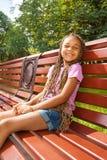 Pequeña muchacha negra agradable que se sienta en banco de e en parque Fotografía de archivo