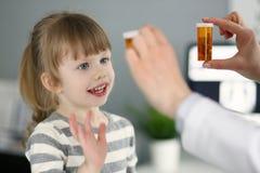 Peque?a muchacha paciente linda que se divierte que selecciona una botella de medicaciones foto de archivo