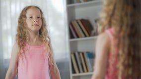Pequeña muchacha pelirroja coquetting delante del espejo, soñando para llegar a ser adulto metrajes