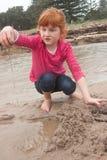 Pequeña muchacha pelirroja que construye un castillo de la arena con la arena mojada en a foto de archivo