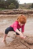 Pequeña muchacha pelirroja que construye un castillo de la arena con la arena mojada en a foto de archivo libre de regalías