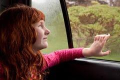 Pequeña muchacha pelirroja que mira hacia fuera la ventanilla del coche en un día de primavera lluvioso imagen de archivo libre de regalías