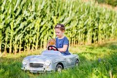 Pequeña muchacha preescolar del niño que conduce el coche grande del juguete y que se divierte con jugar con el oso grande del ju Foto de archivo
