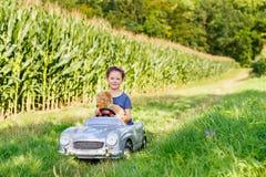 Pequeña muchacha preescolar del niño que conduce el coche grande del juguete y que se divierte con jugar con el oso grande del ju Fotografía de archivo libre de regalías