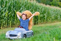 Pequeña muchacha preescolar del niño que conduce el coche grande del juguete y que se divierte con jugar con el oso grande del ju Fotografía de archivo