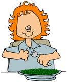 Pequeña muchacha que come los guisantes Fotografía de archivo