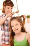 Pequeña muchacha que consigue el peine del pelo Imagen de archivo