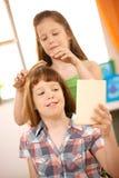 Pequeña muchacha que consigue el peine del pelo Foto de archivo libre de regalías