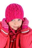 Pequeña muchacha que estira su casquillo del invierno sobre blanco Fotografía de archivo