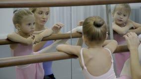 Pequeña muchacha que hace estirar con el profesor en escuela del ballet almacen de metraje de vídeo