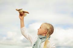 Pequeña muchacha que juega con con el juguete contra el cielo Imágenes de archivo libres de regalías