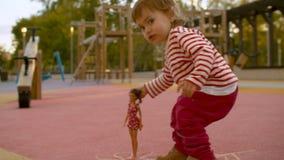 Pequeña muchacha que juega con la muñeca almacen de metraje de vídeo