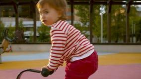 Pequeña muchacha que juega en el oscilación de madera almacen de video