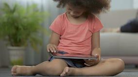 Pequeña muchacha que juega a juegos en la tableta que se sienta en piso en casa, educación preescolar almacen de video