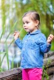 Pequeña muchacha que lleva en la camisa del dril de algodón que presenta cerca de la charca fotografía de archivo libre de regalías