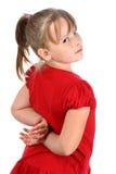Pequeña muchacha que mira sobre el hombro aislado en blanco Foto de archivo libre de regalías