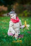 Pequeña muchacha que se sienta en la hierba en el parque Imagenes de archivo