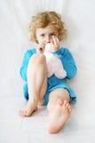 Pequeña muchacha que se sienta rizada rubia triste en el blanco con el juguete Imagen de archivo