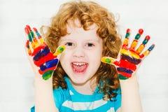Pequeña muchacha rizada feliz con las manos en la pintura Imagen de archivo libre de regalías