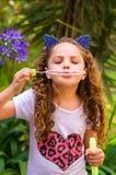 Pequeña muchacha rizada feliz que juega con las burbujas de jabón en una naturaleza del verano, el llevar oídos azules de los acc Foto de archivo libre de regalías