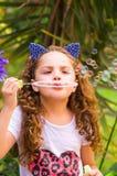 Pequeña muchacha rizada feliz que juega con las burbujas de jabón en una naturaleza del verano, el llevar oídos azules de los acc Imagenes de archivo