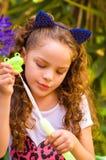 Pequeña muchacha rizada feliz que juega con las burbujas de jabón en una naturaleza del verano, el llevar oídos azules de los acc Imágenes de archivo libres de regalías