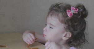 Pequeña muchacha rizada que come la panadería de la paja almacen de video