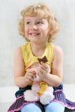 Pequeña muchacha rizada rubia que come el chocolate con el juguete Fotos de archivo