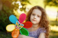 Pequeña muchacha rizada triste que sostiene un molinillo de viento del arco iris Imagen de archivo libre de regalías