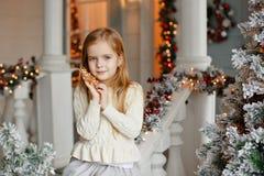 Pequeña muchacha rubia adorable con los ojos azules que sonríe en el interio Fotos de archivo libres de regalías