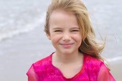 Pequeña muchacha rubia con el océano detrás de ella Imagenes de archivo