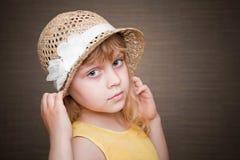 Pequeña muchacha rubia con el sombrero de paja agradable Foto de archivo