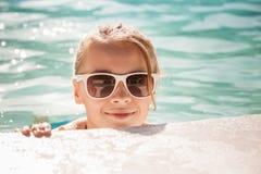 Pequeña muchacha rubia con las gafas de sol en piscina al aire libre Imagen de archivo libre de regalías
