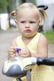 pequeña muchacha rubia con los ojos azules en la bicicleta imágenes de archivo libres de regalías