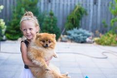 Pequeña muchacha rubia con su perro casero al aire libre adentro Imagenes de archivo