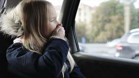 Pequeña muchacha rubia en asientos traseros en coche almacen de video