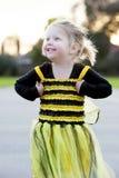 Pequeña muchacha rubia en el traje de la abeja que baila al aire libre Imagen de archivo libre de regalías